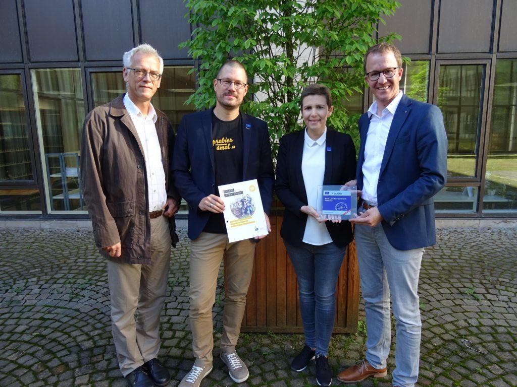 Landesrat Christian Gantner freut sich mit Karin Feurstein-Pichler, Wolfgang Seidel und Josef Burtscher über die Auszeichnung für Probier amol.