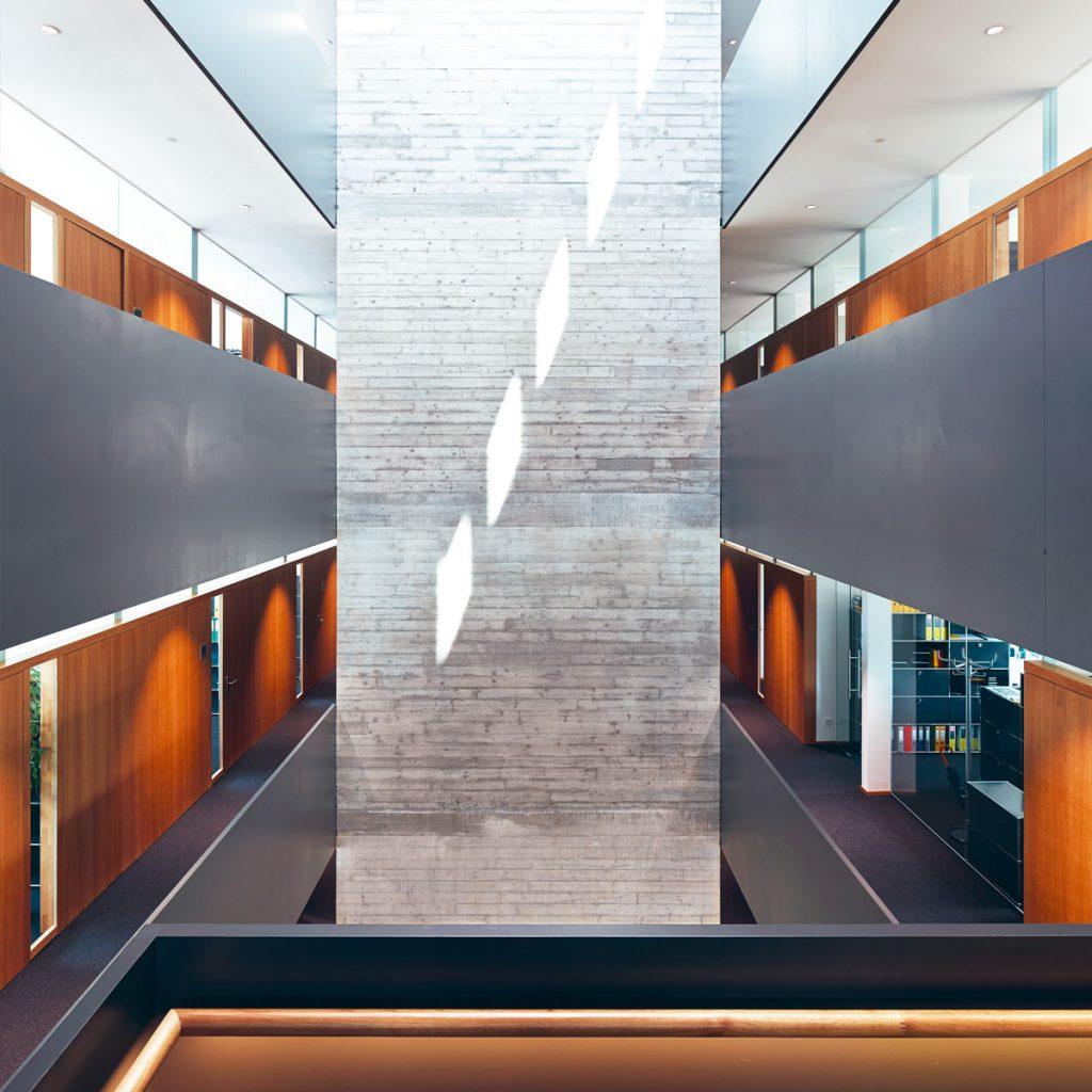 Das Atrium im Bürogebäude der i+R Gruppe sorgt für die notwendige sanfte Thermik, damit die Kaskadenlüftung funktioniert. Bildnachweis: Bruno Klomfar