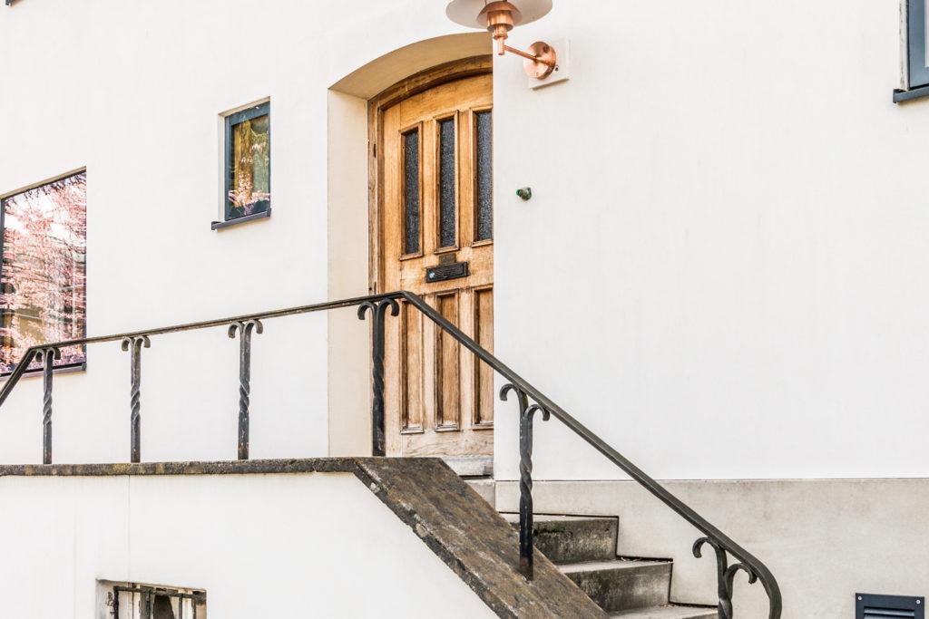Neu trifft Original: Während der Sockel und die Fassade thermisch saniert und erneuert wurden, blieben die Haustüre, Treppe und Vorplatz im noch guten Originalzustand.