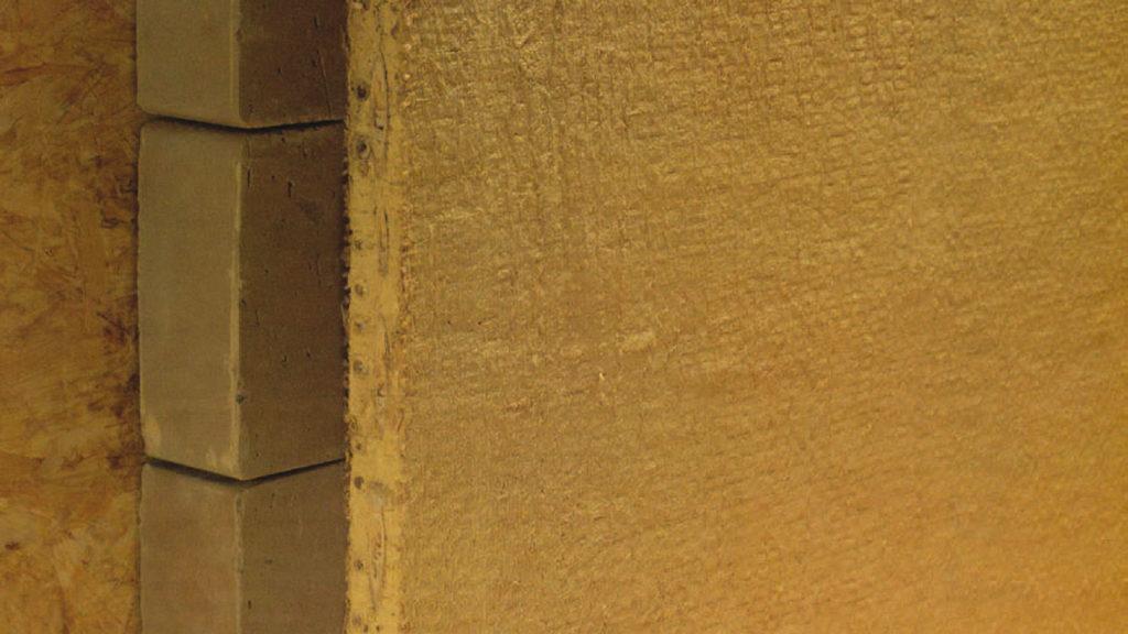 Ein Wandaufbau mit Holzplatte, Lehmstein, Lehmbauplatte.