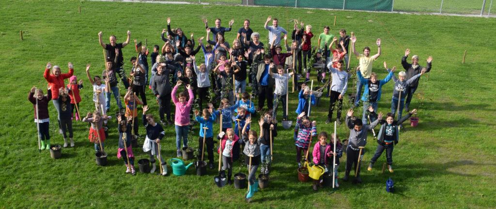 Das Bild zeigt eine große Kindergruppe mit Schaufeln, Eimern und Gießkannen. Die Kinder heben ihre Hände und haben sichtlich Freude beim Anlegen der Baumschule an der neuen Schule am See.