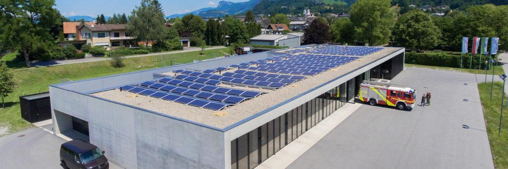 Das Bild zeigt ein Feuerwehrhaus mit einer großen Photovoltaikanlage auf dem Dach. Vor dem Gebäude steht ein Feuerwehrauto und mehrere Personen.