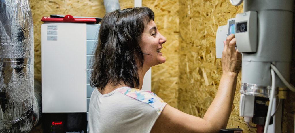 Eine Frau ließt den Energieverbrauch an einem Zähler ab und freut sich sichtlich über die Einerzielten Einsparungen.